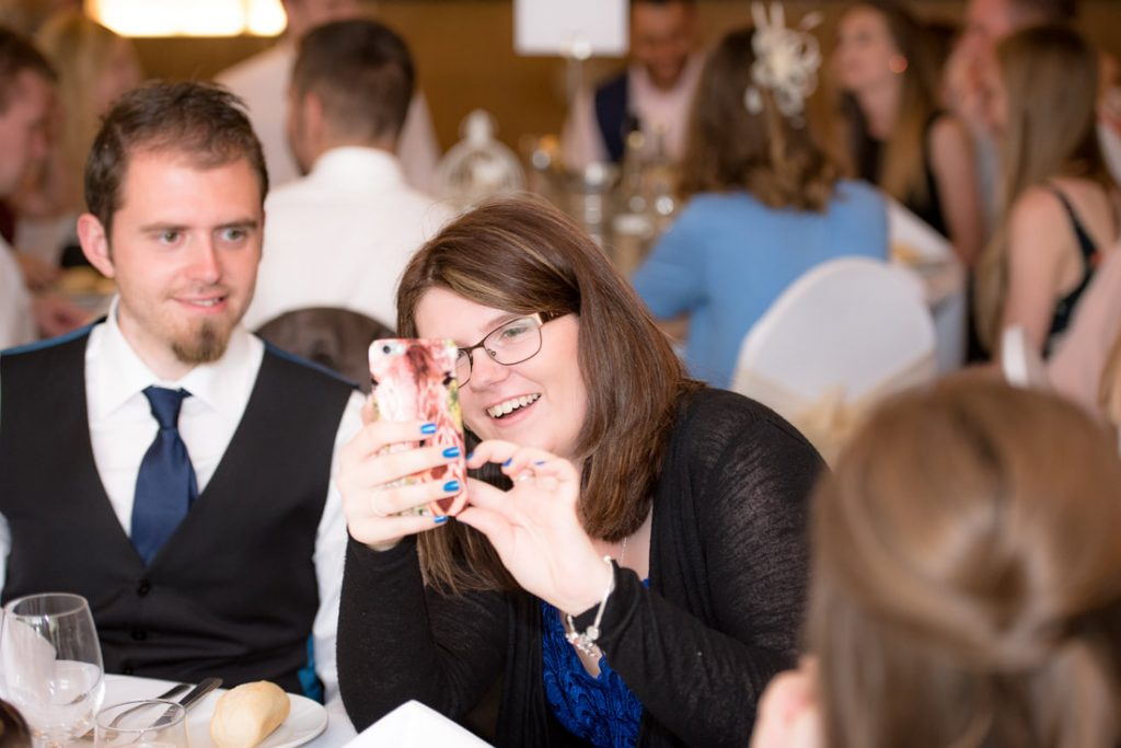 A guest takes a photo on her phone