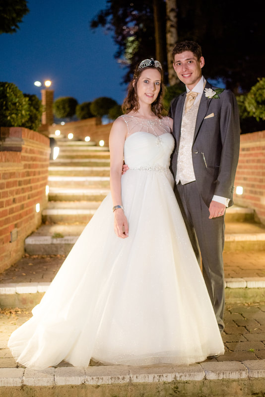 The bride and groom pose on the steps of Great Hallingbury Manor