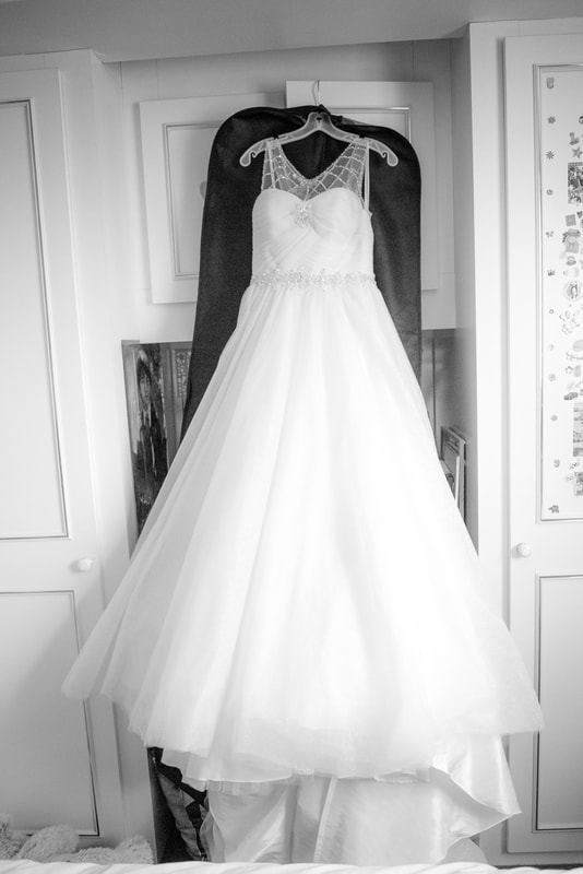 The wedding dress hangs up against the wardrobe