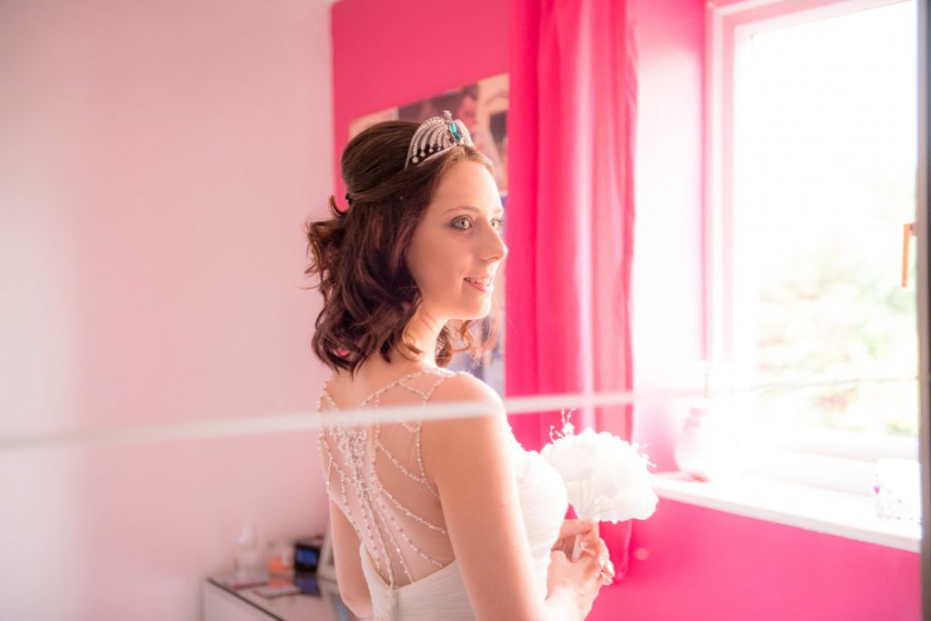 The bride looks at her reflection in the wardrobe mirror