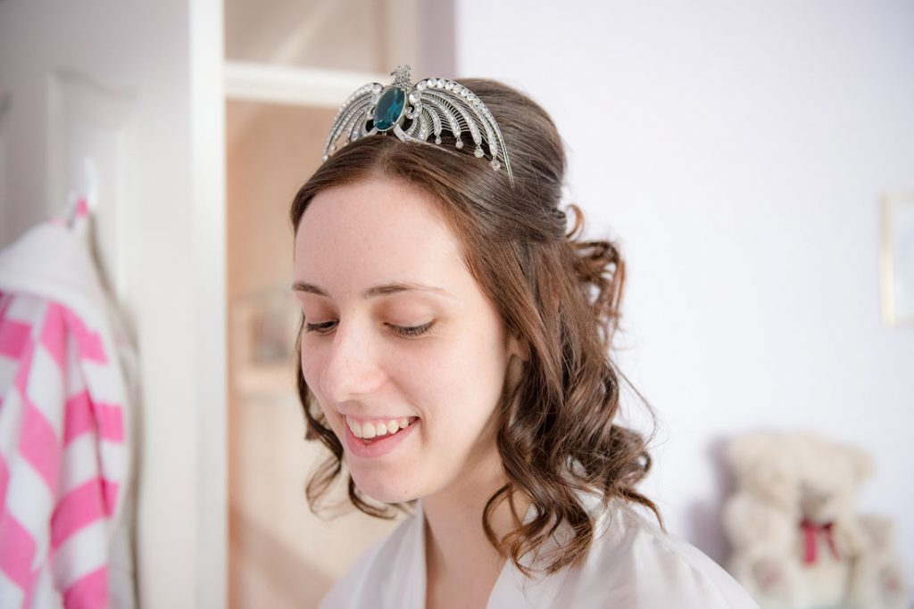 The bride smiles as she puts on her makeup
