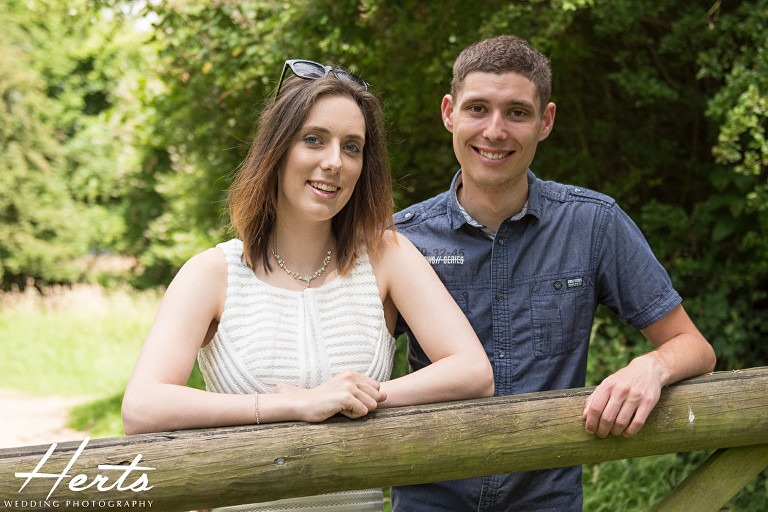 The couple lean on a wooden gate