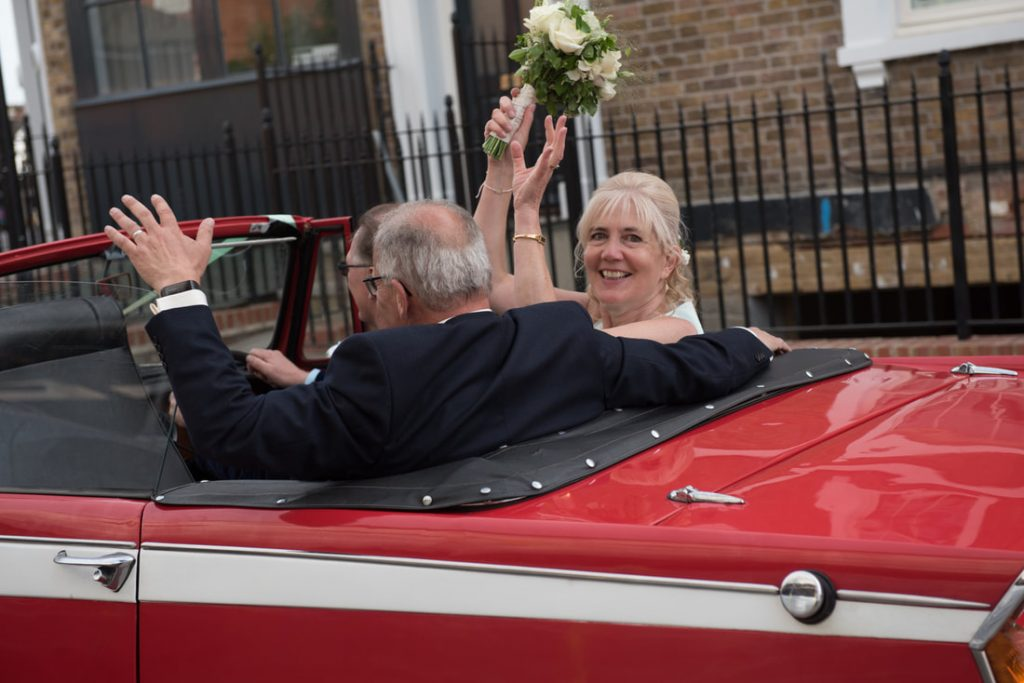 The bride and groom leaving in their wedding car