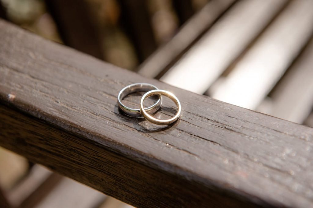 The wedding rings on a wooden brown bench