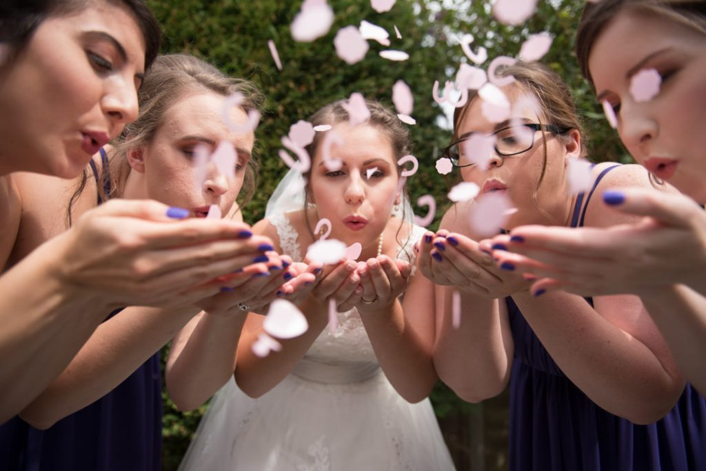 The bridal party blowing confetti