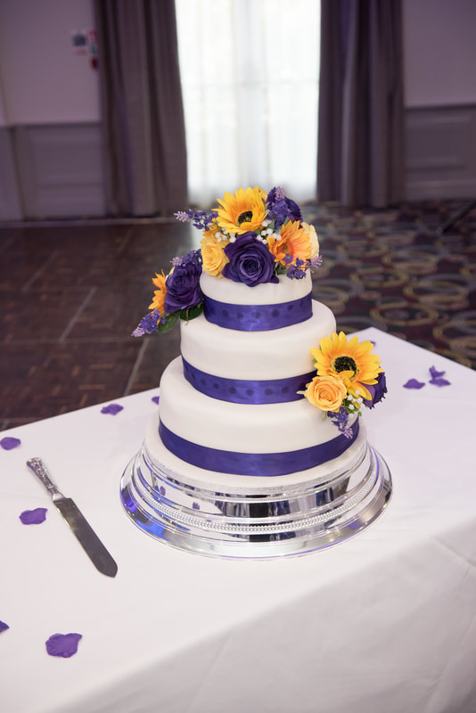 A 3 tier wedding cake with purple ribbons