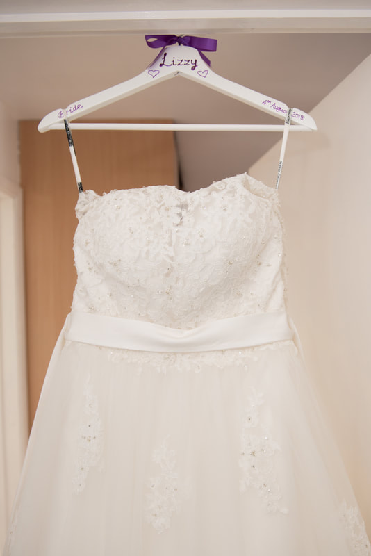 The wedding dress hanging from the door frame