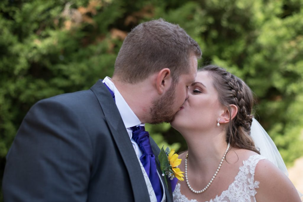 The bride and groom kiss in the gardens of the letchworth mercure hotel