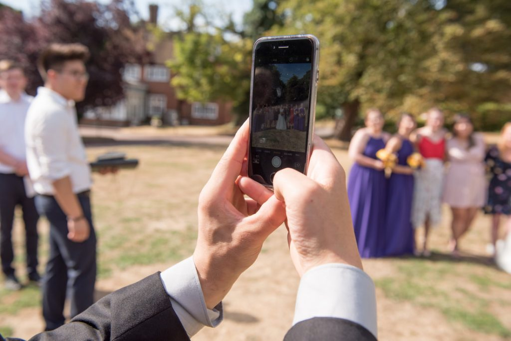 A wedding guest taking a picture on a mobile phone