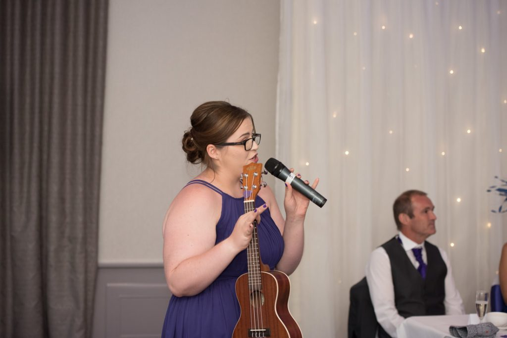 The bridesmaid performing a song for the bride and groom