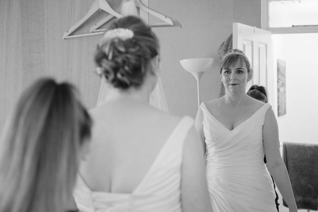 The bride looking at her dress in the mirror