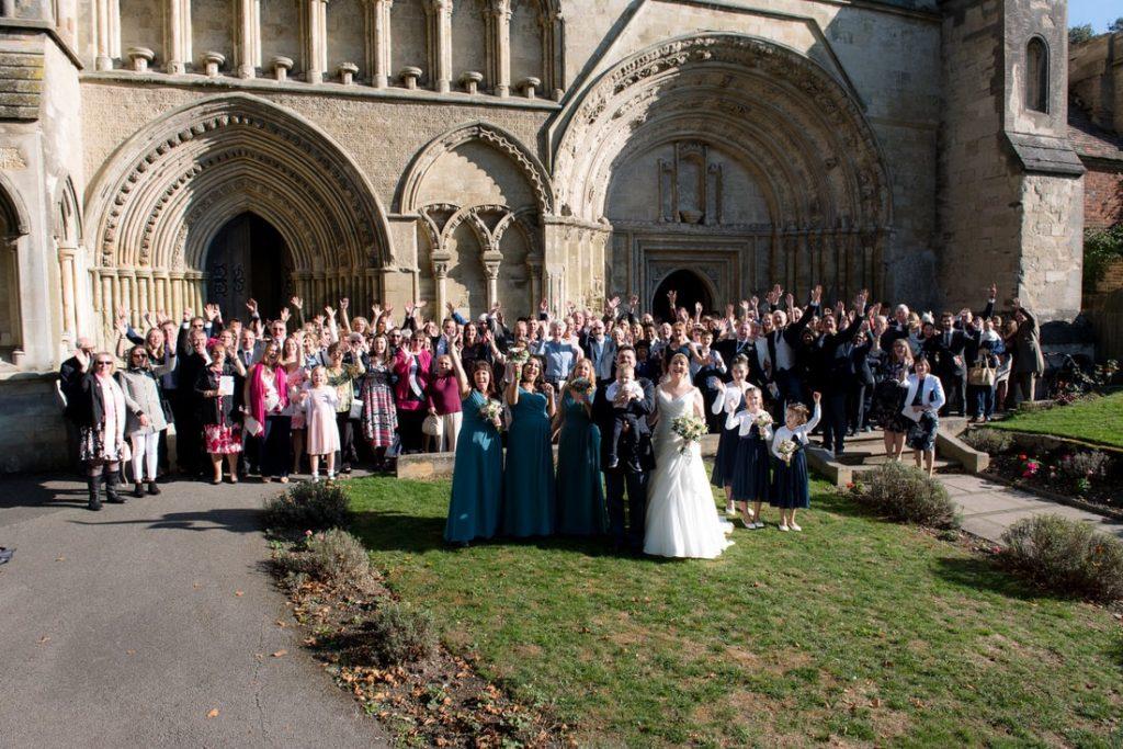 Wedding guests waving at the camera