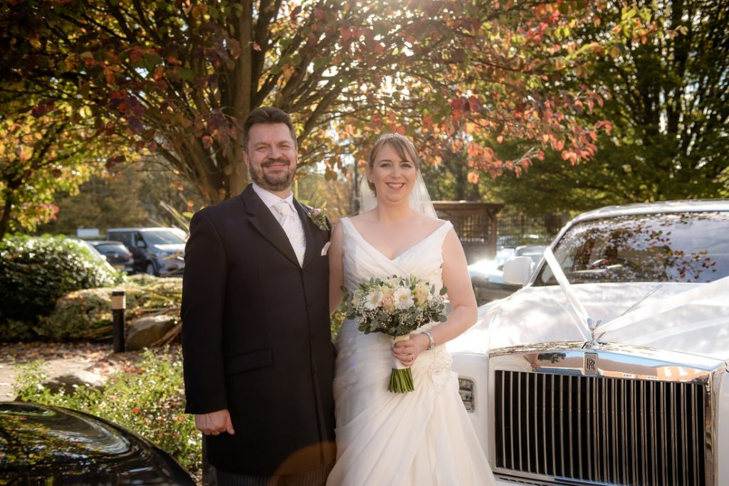 The bride and groom beside a wedding car outside Mitchell Hall