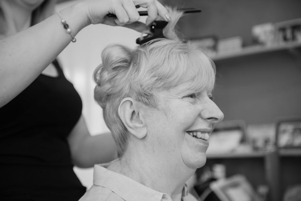 The mother of the bride having her hair styled