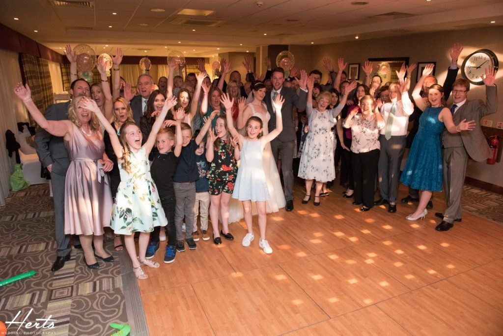 All of the wedding guests wave at the camera