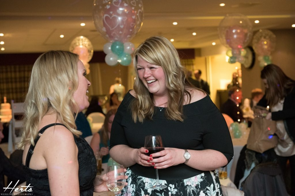 Wedding guests enjoy a joke together at a Stevenage Holiday Inn Wedding