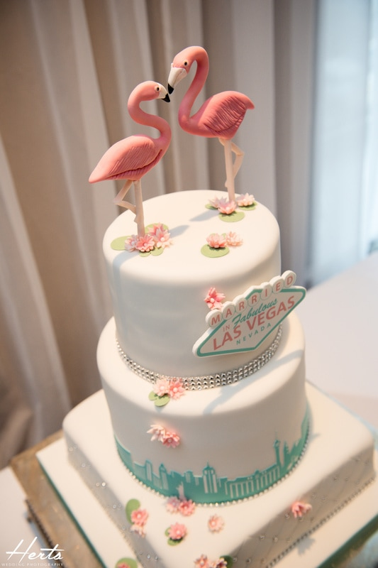 A wedding cake with flamingos on top