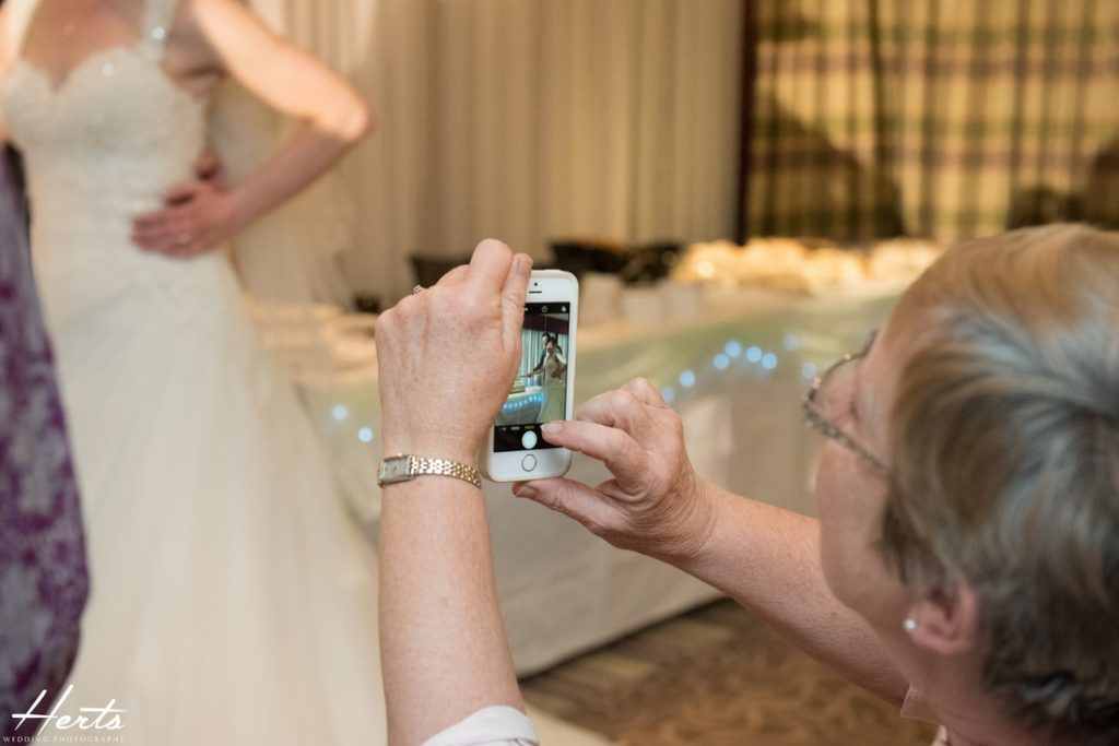 A guest takes a photo of the cake cutting