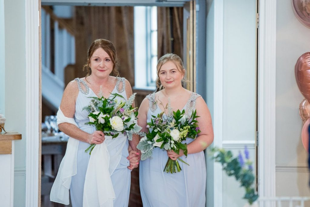 Bridesmaids entering the dairy barn