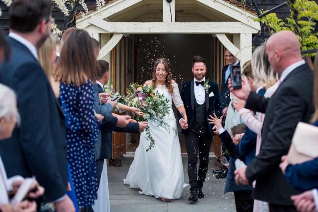 The bride and groom walk into the confetti