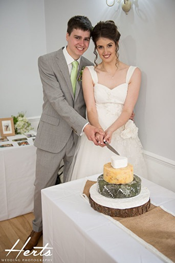 The bride and groom cut the cheese cake together