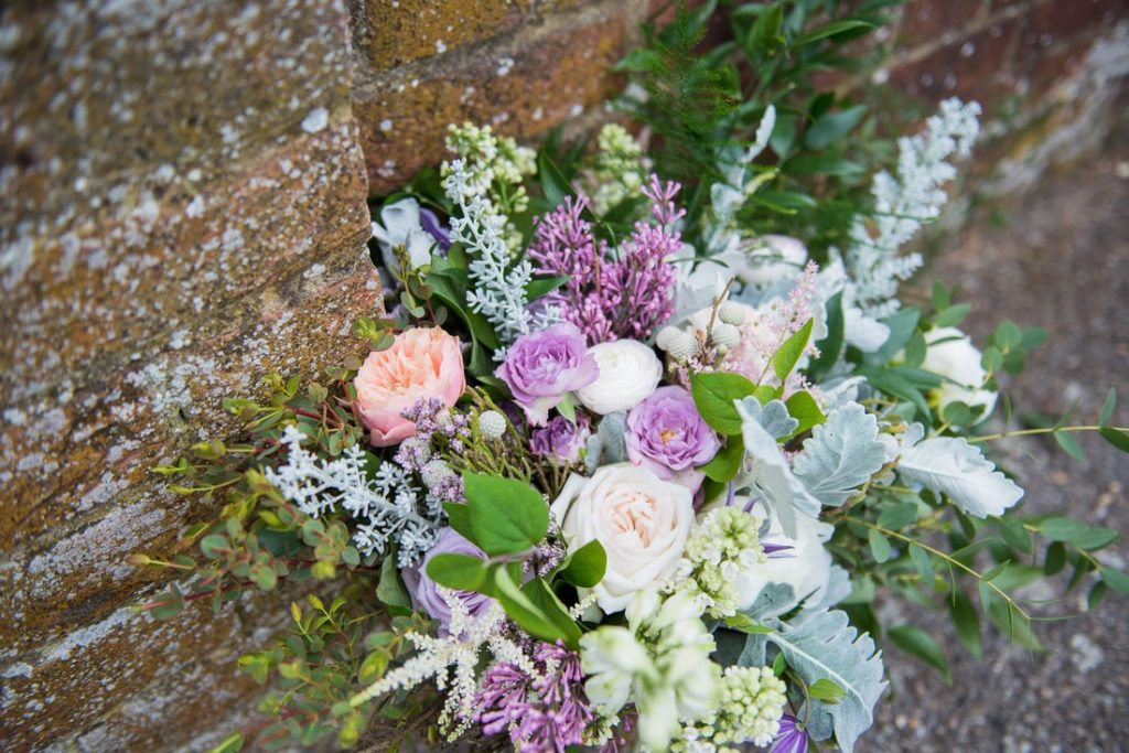 The bridal bouquet by a red brick wall