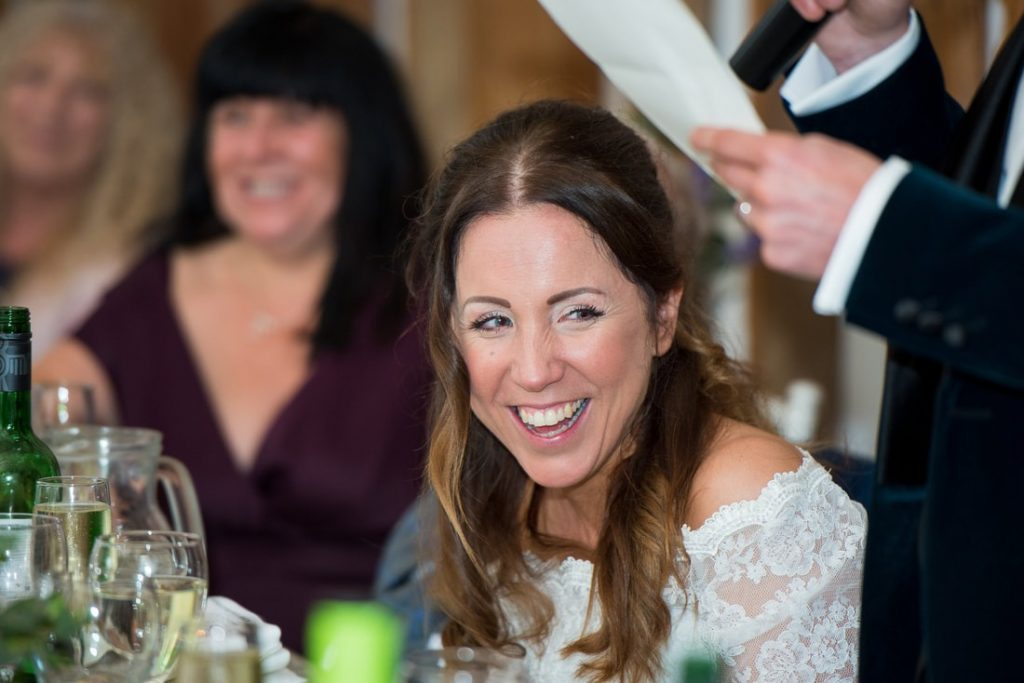 The bride laughs at the jokes in the speeches