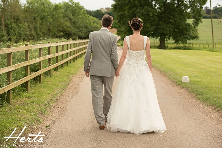 The bride and groom walk down a country lane