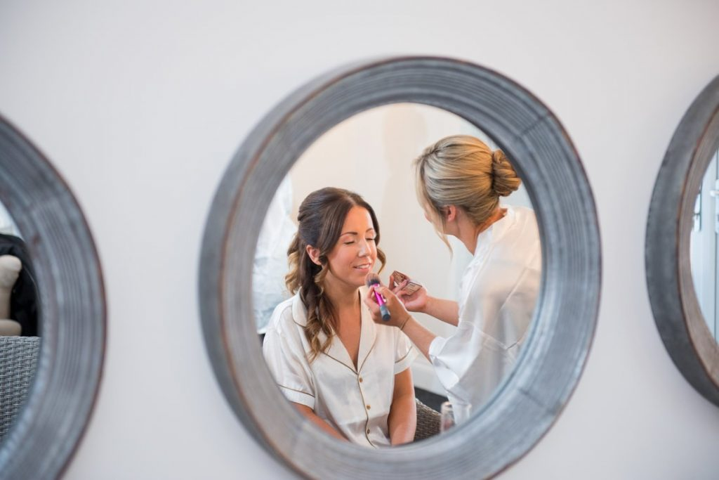 The brides makeup being applied in a mirror
