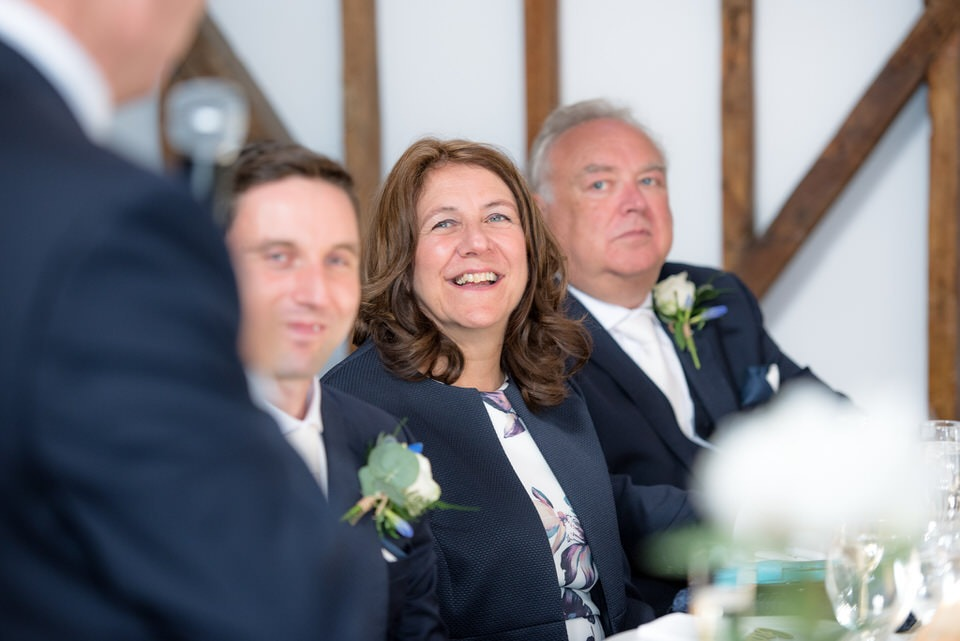 The mother of the bride smiling during the speech