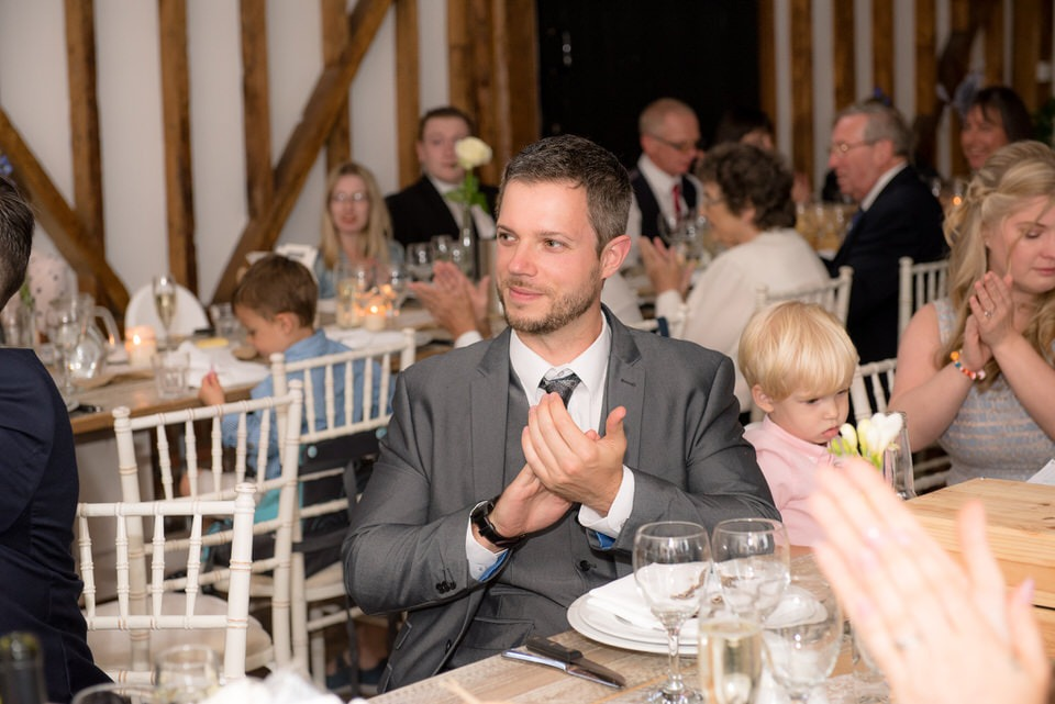 A wedding guest applauding the bride and groom