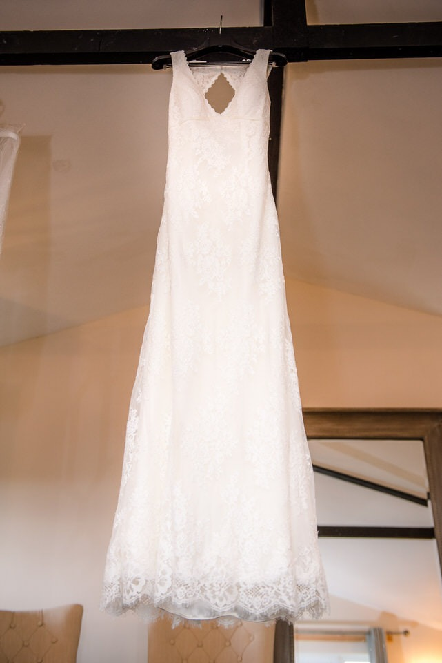 The wedding dress hanging from the beams