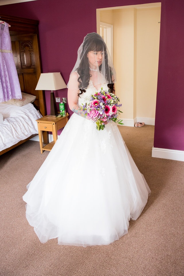 The bride stands with her bouquet of flowers