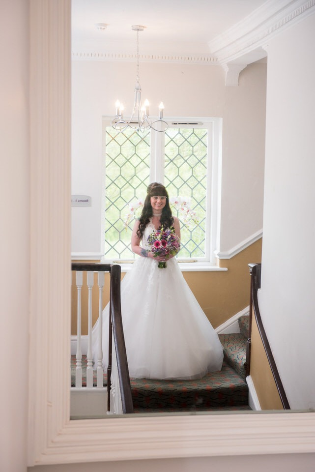 The bridesmaid standing opposite the mirror