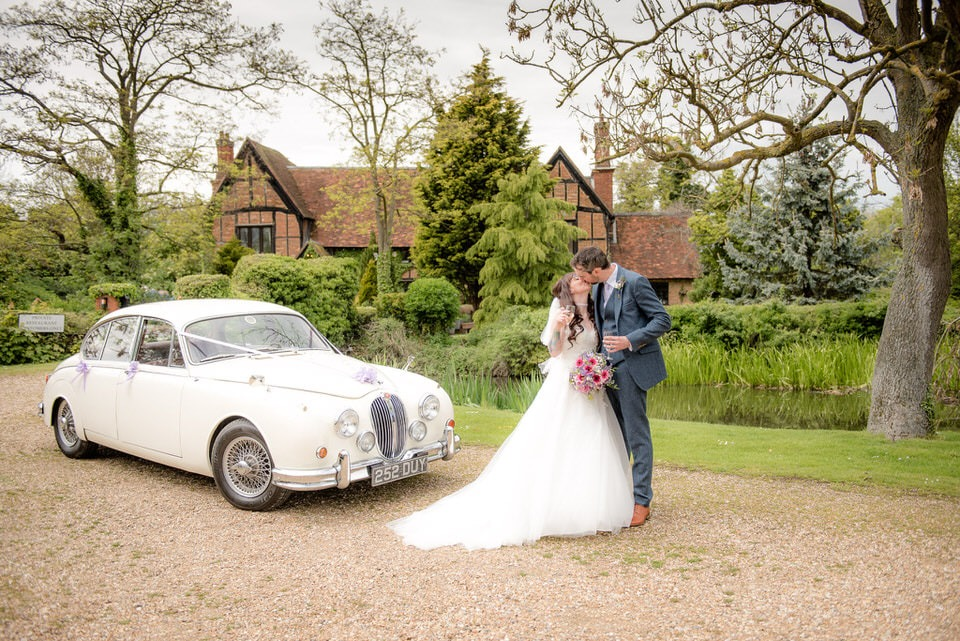 The bride and groom with the wedding car