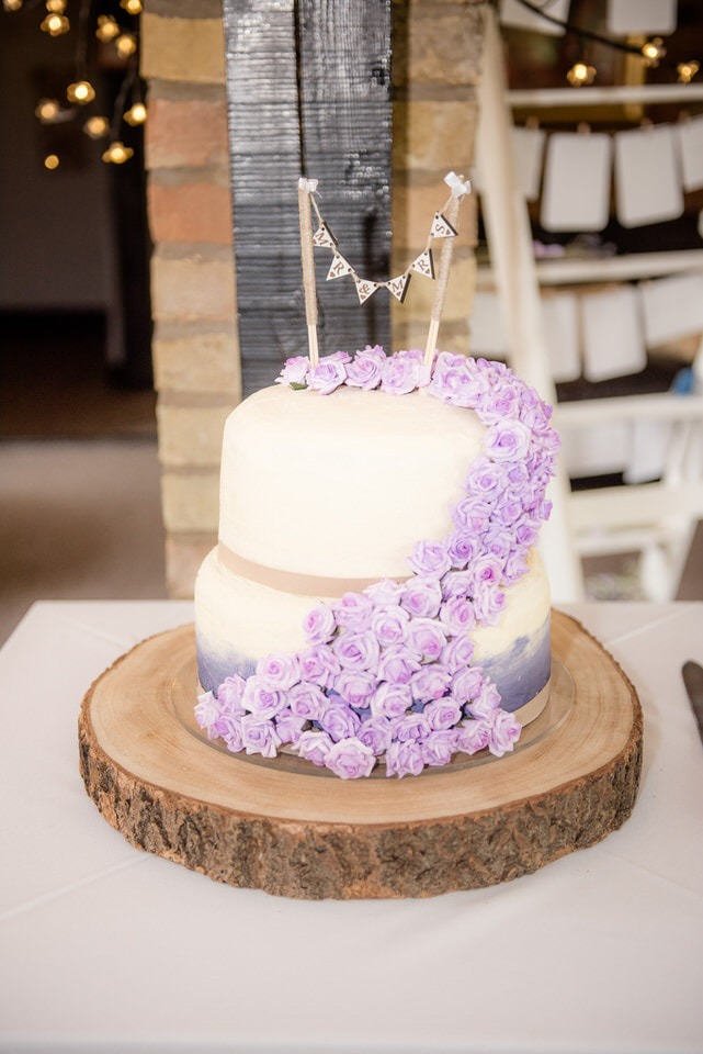 Homemade wedding cake dressed in purple icing flowers