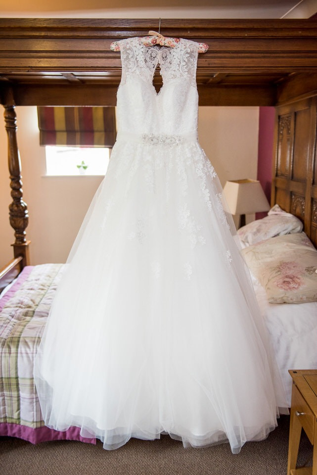 Wedding dress hanging from the four poster bed