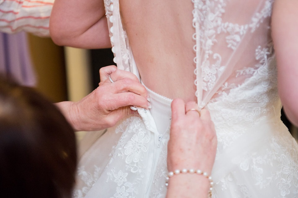 The back of the wedding dress being buttoned up