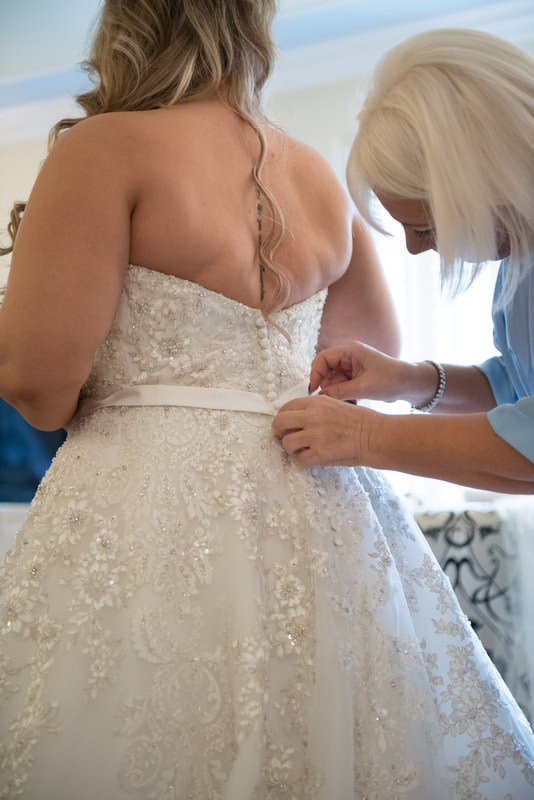 The mother of the bride puts the finishing touches to the wedding dress