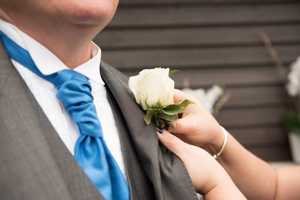 A buttonhole being attached to the suit of the father of the bride