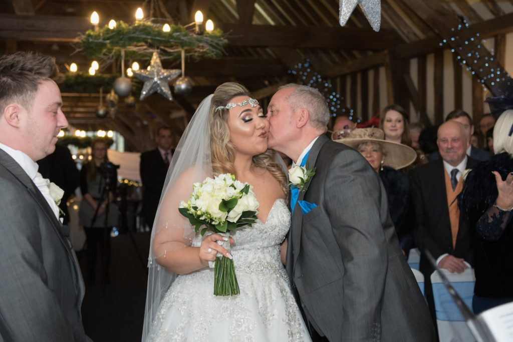The father of the bride gives his daughter a kiss on the cheek