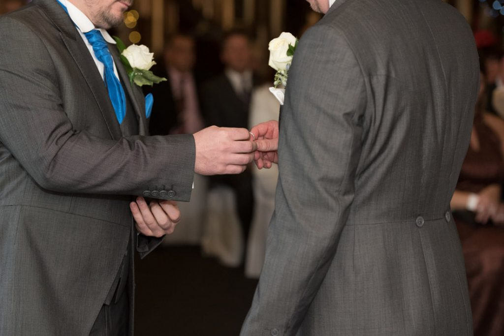 The best man passes the groom the wedding ring for the bride
