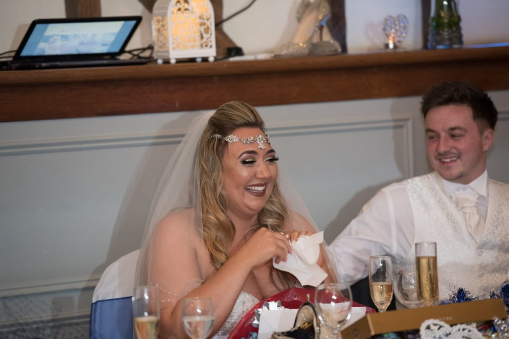 The bride uses a tissue to wipe away the tears of laughter