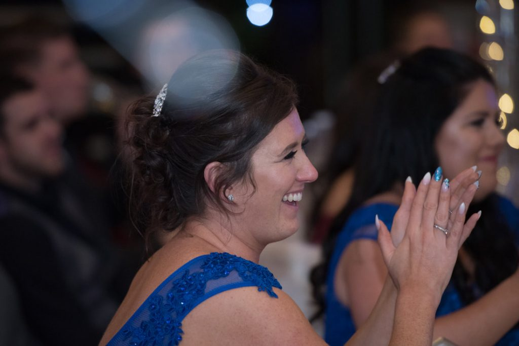 A wedding guest applauds the wedding speeches