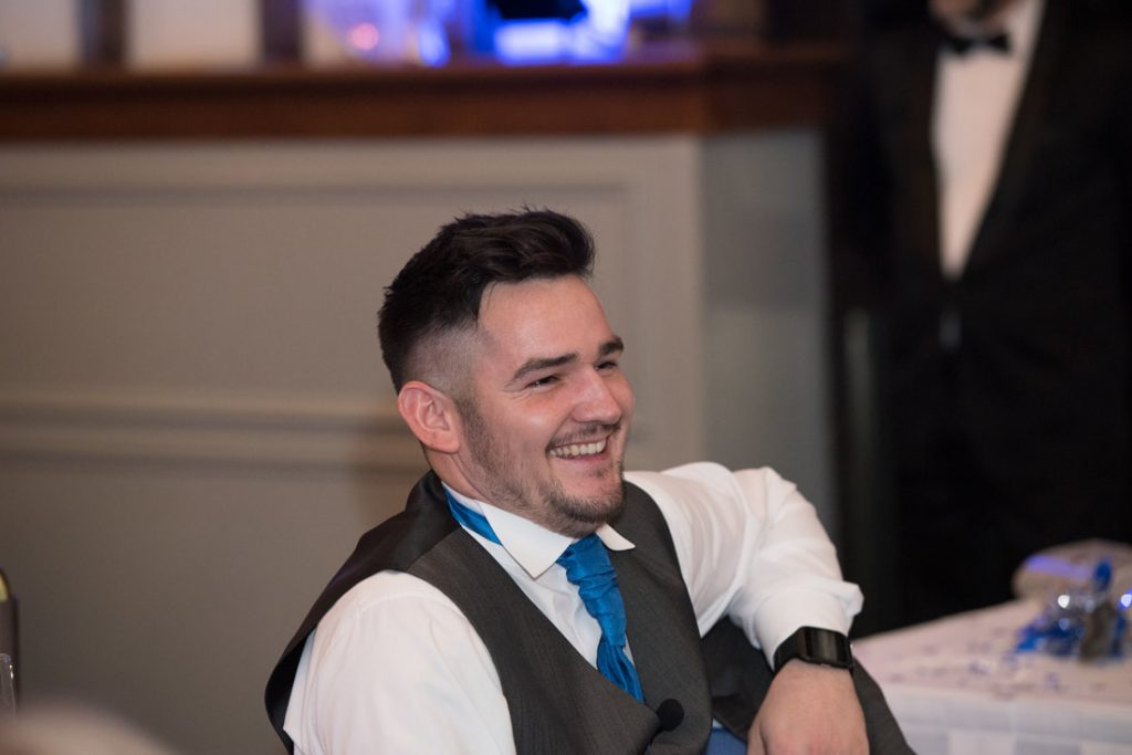 The best man sits laughing