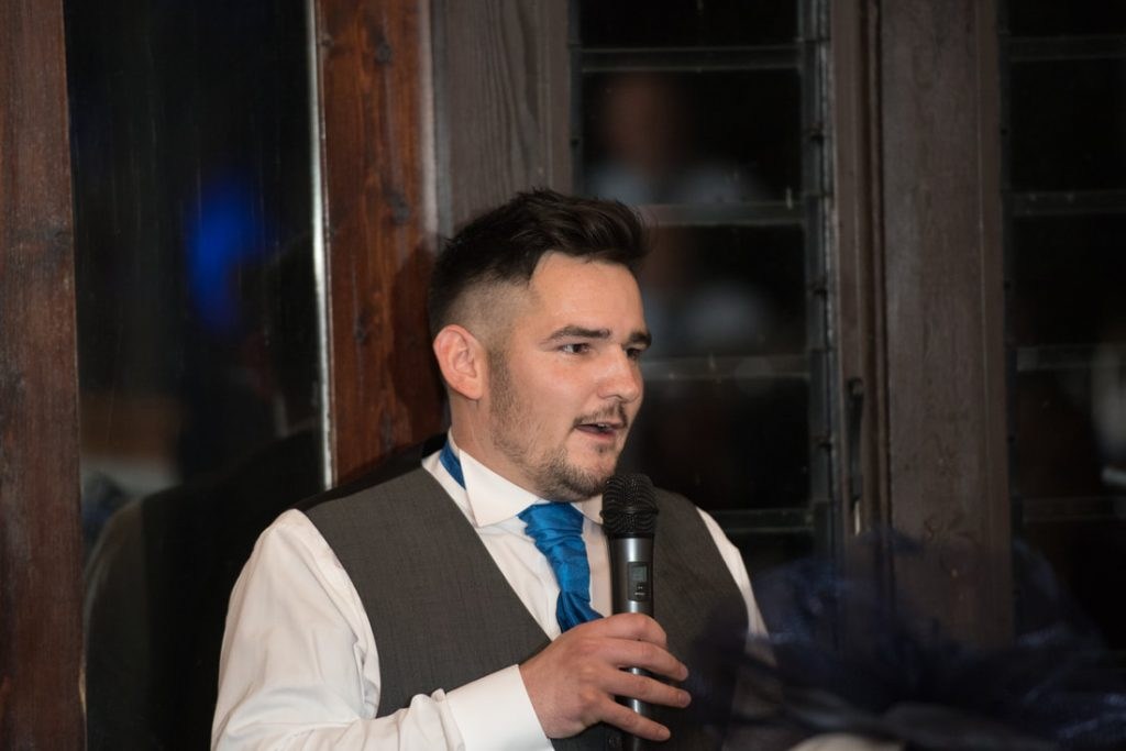 The best man holds a microphone whilst delivering his speech about the groom
