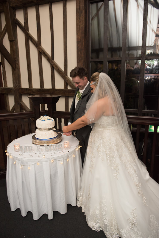 The happy couple cutting into the wedding cake