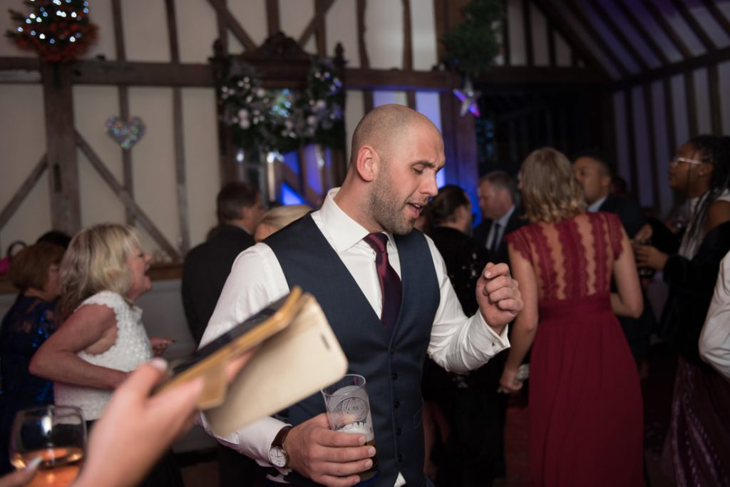 A wedding guest dancing with his drink