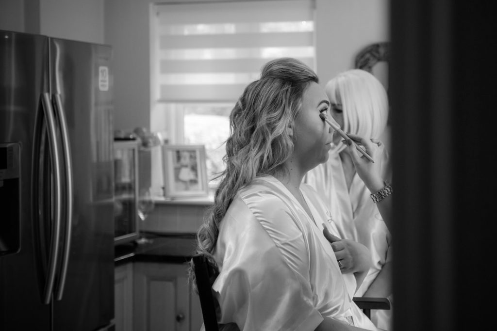 A black and white shot of makeup being put on the bride