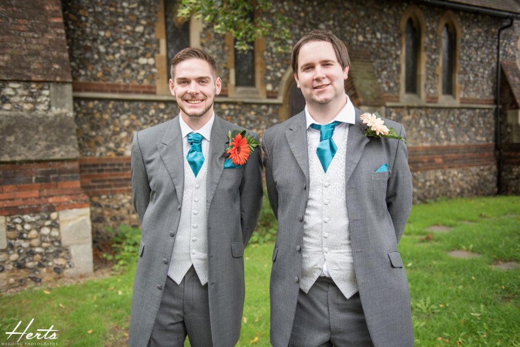 The groom and his best man stand outside the church